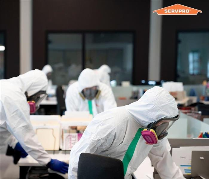 The image shows SERVPRO employees in hazmat suits sanitizing a facility